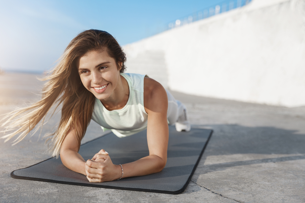 Woman smiling in a plank position