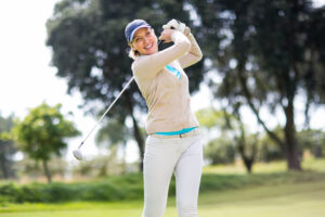 Female golfer taking a shot on a sunny day at the golf course
