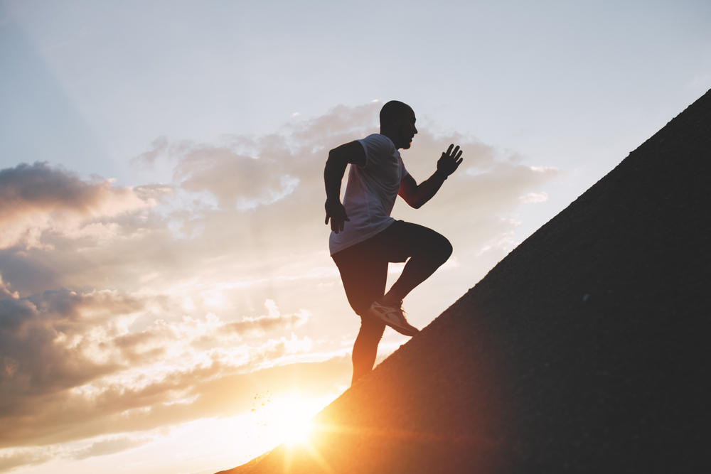 Man running uphill at sunset