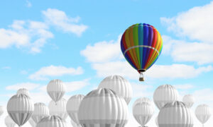 A colorful hot air balloon rising above a sea of white hot air balloons