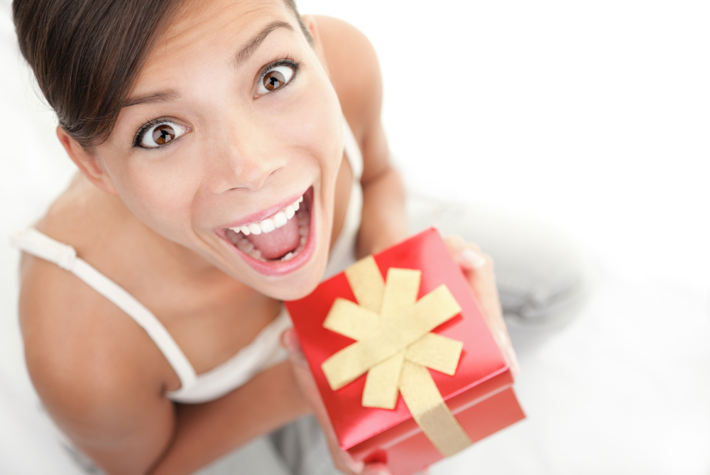 A woman is excited about the gift she is holding