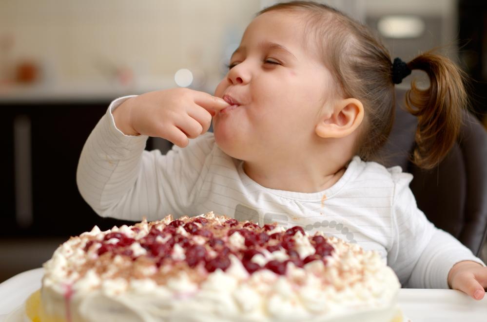Cute little girl tasting cake