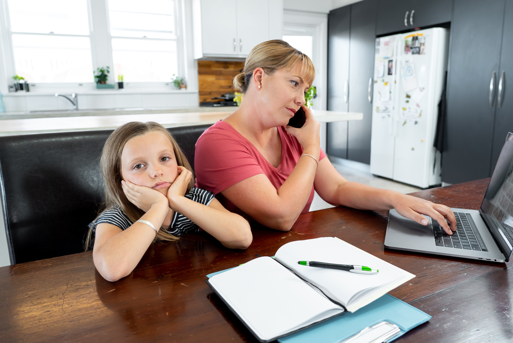 a busy mom is on the phone and looking at her laptop at the kitchen table while her daughter waits for help with homework