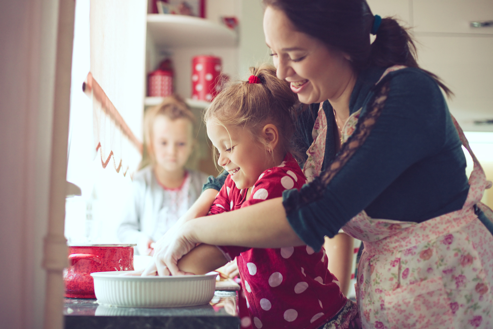 Mother with her 5 years old kids cooking a holiday pie in the kitchen