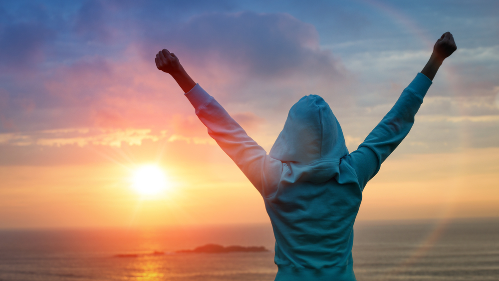 A woman in a hoodie with her arms outstretched in the sunset.