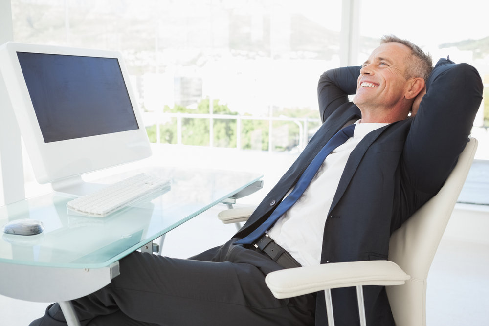 A happy business man enjoying his time at work in a beautiful modern office