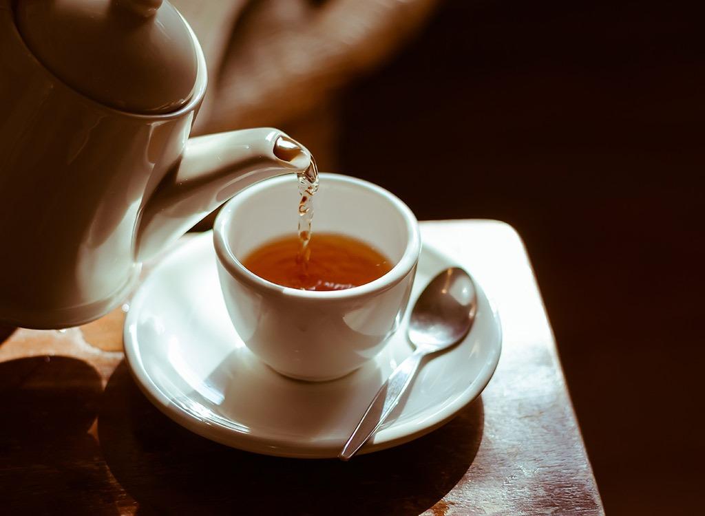 A kettle pouring tea into a teacup