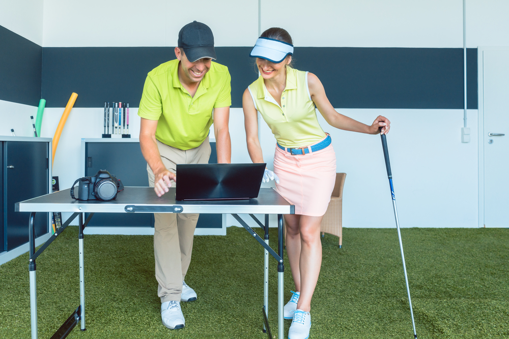A happy golfing couple is looking at a laptop that is sitting on a folding table on top of an artificial practice green.