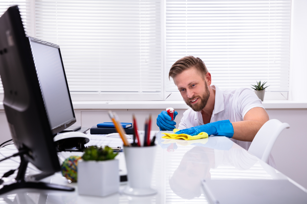 A man wearing blue gloves is wiping down his white modern desk
