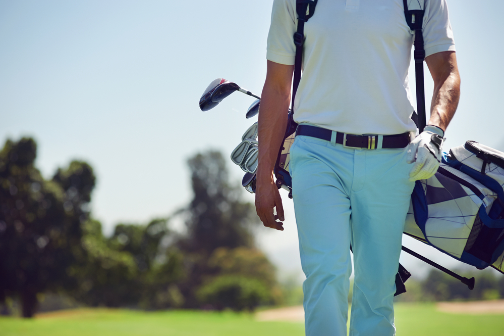 Golf player walking and carrying bag on course during