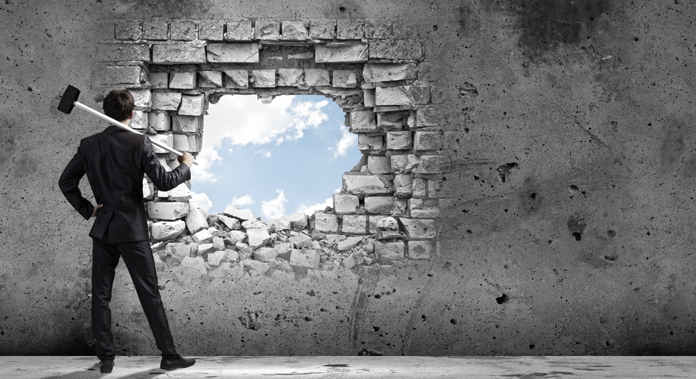 A business professional with a sledge hammer looks through an opening in a wall where you see blue sky