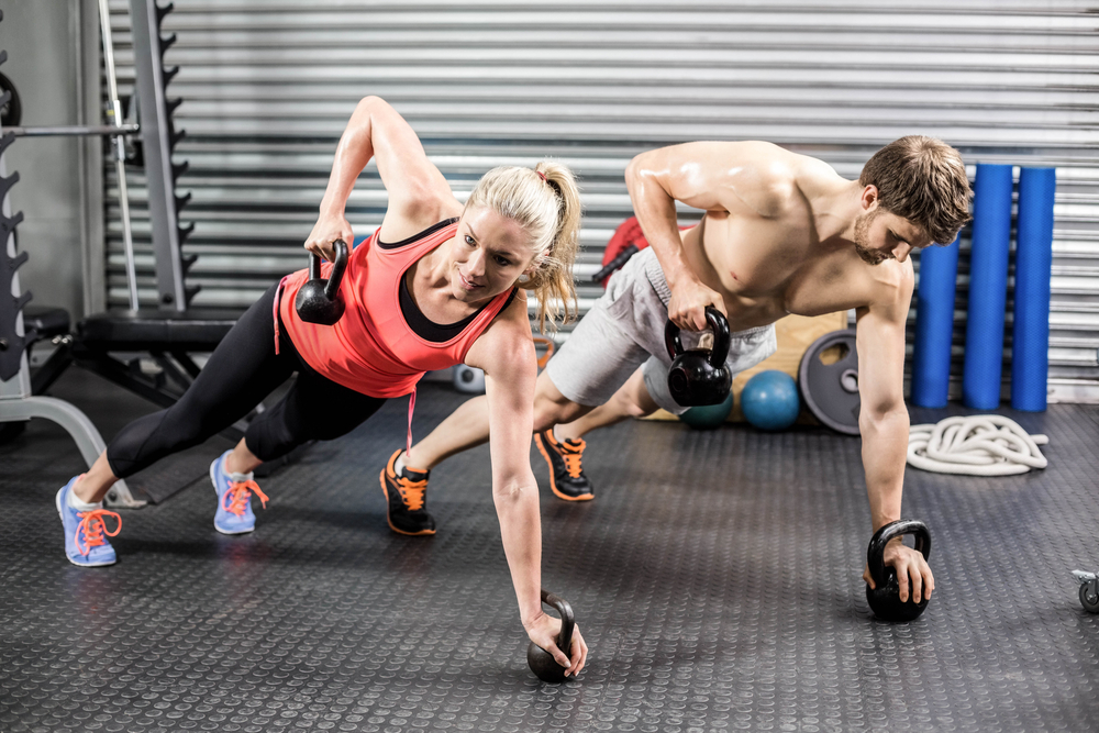 A couple is doing plank and kettle bell exercises together