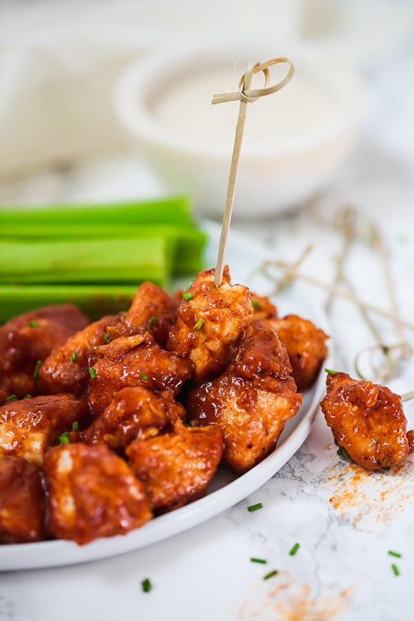 BBQ chicken poppers on a plate with a toothpick and celery