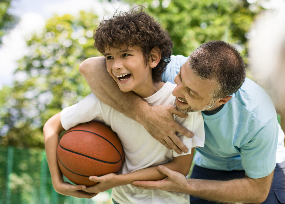 Happy Loving Family. Portrait of laughing dad hugging his curly son from the back, boy holding basket ball