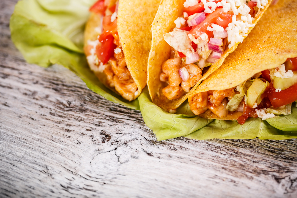 Tacos with chicken on wooden table