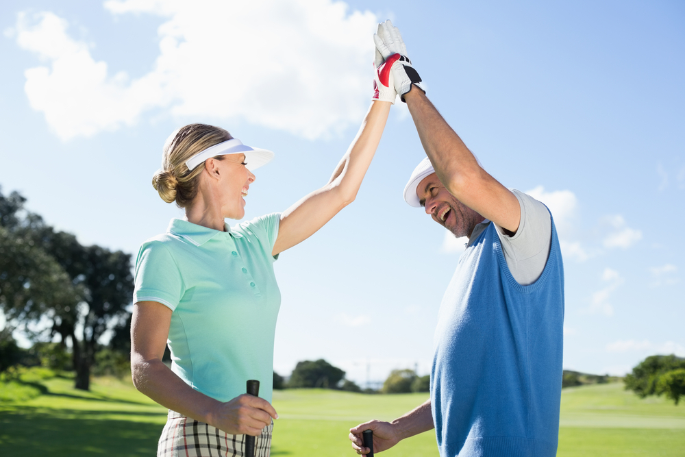 Competitive female golfer giving her coach a high five on the golf course.