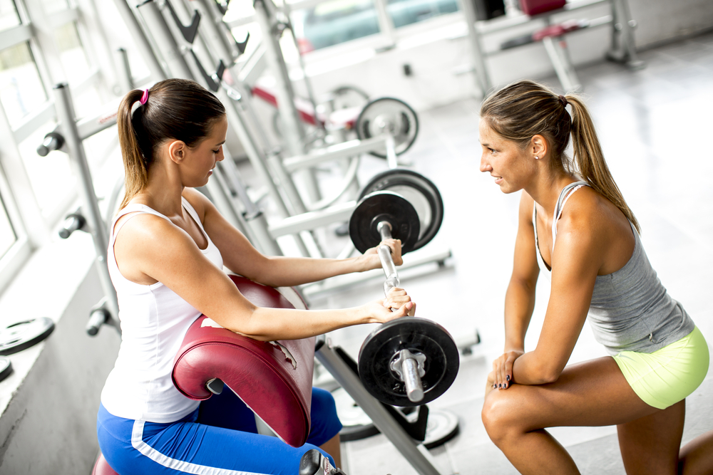 A young woman is performing a bar curl in front of a female fitness instructor