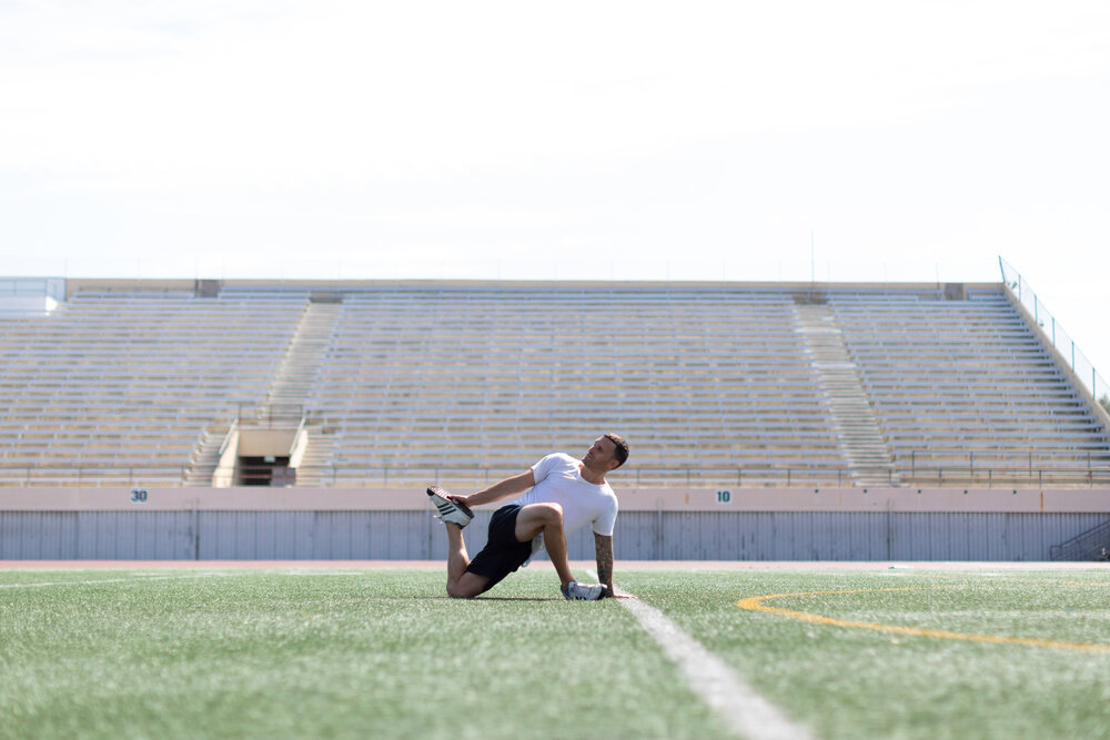Man on field stretching his knees
