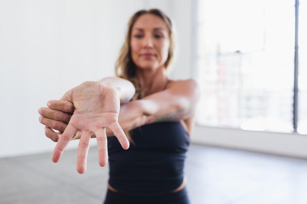 Woman performing wrist stretch.