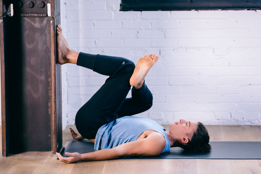 Woman on her back stretching her knees against a wall