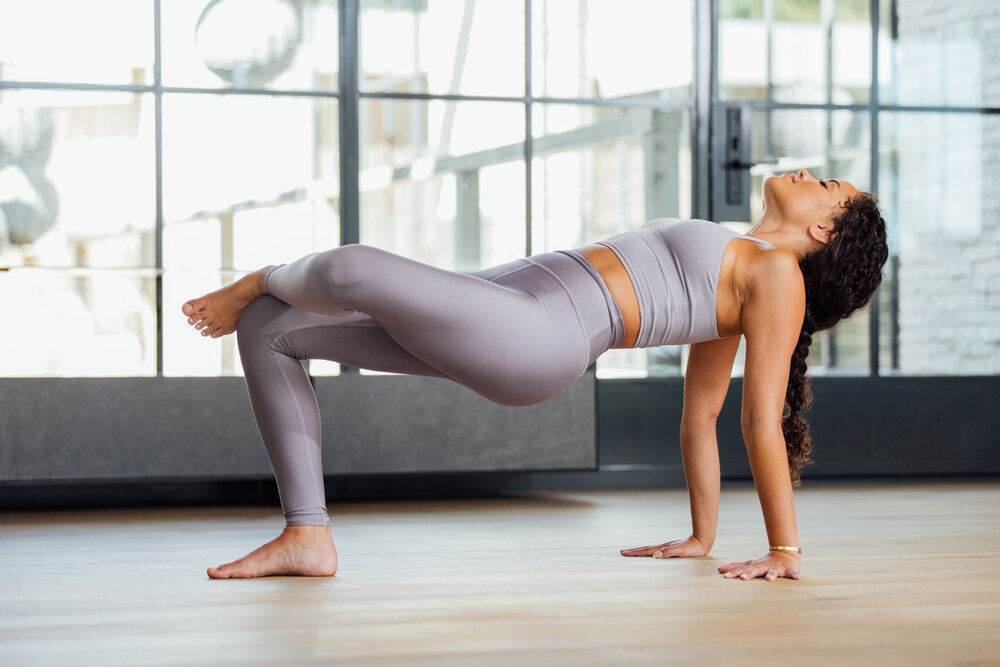 Woman stretching knees while lifted by hands and leg on ground