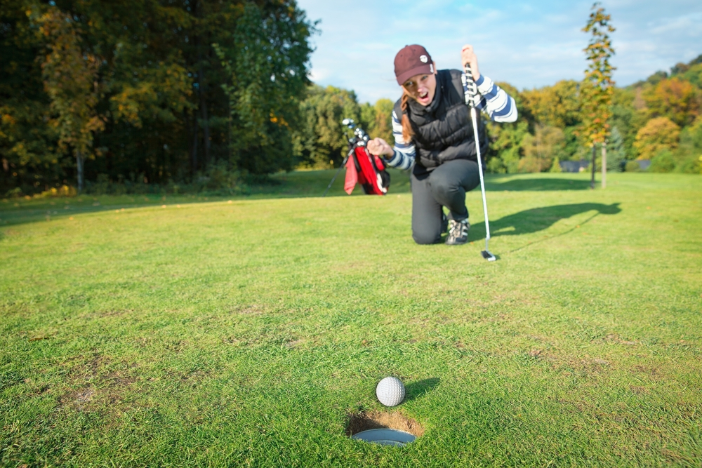 A female golfer is excited about her ball that is on the edge of the hole