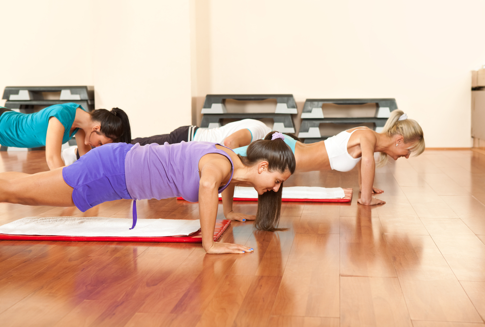 young people in gym exercising, doing push-ups